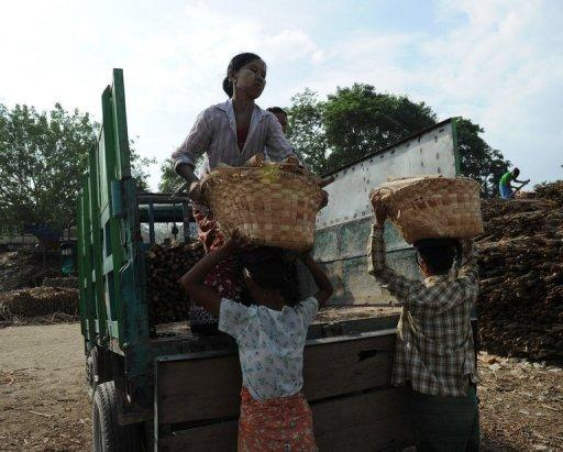 Women load wood into a truck to later be sold as firewood in Myanmar. A US ban on all Myanmar imports is stifling key job-creating areas of the economy such as the garment industry rather than hurting the interests of the corrupt elite it targets, a report said Friday