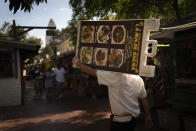 Restaurant worker Abraham Ordaz, 38, carries a menu stand along Olvera Street in Los Angeles, Tuesday, June 8, 2021. Olvera Street has long been a thriving tourist destination and a symbol of the state's early ties to Mexico. The location of where settlers established a farming community in 1781 as El Pueblo de Los Angeles, its historic buildings were restored and rebuilt as a traditional Mexican marketplace in 1930s. As Latinos in California have experienced disproportionately worse outcomes from COVID-19, so too has Olvera Street. (AP Photo/Jae C. Hong)