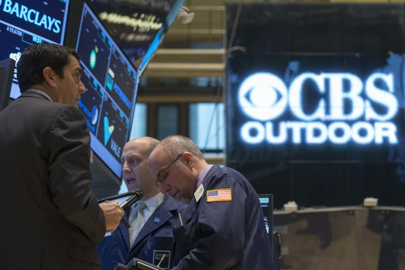 Traders work as a logo for CBS Outdoor is displayed prior to the company's IPO on the floor of the New York Stock Exchange