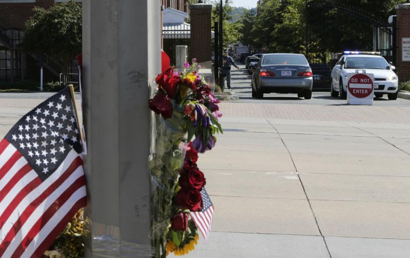 A U.S. flag and flower memorial is shown across the street from the Washington Navy Yard September 19, 2013. Thousands of workers streamed back into the Washington Navy Yard on Thursday, three days after a former reservist working at the site as a contractor opened fire with a shotgun as he wandered several floors and hallways, killing 12 people. REUTERS/Gary Cameron (UNITED STATES - Tags: CIVIL UNREST MILITARY)