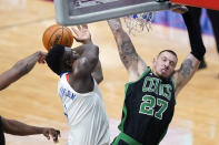 New Orleans Pelicans forward Zion Williamson is stripped of the ball as he drives to the basket against Boston Celtics center Daniel Theis (27) in the first half of an NBA basketball game in New Orleans, Sunday, Feb. 21, 2021. (AP Photo/Gerald Herbert)