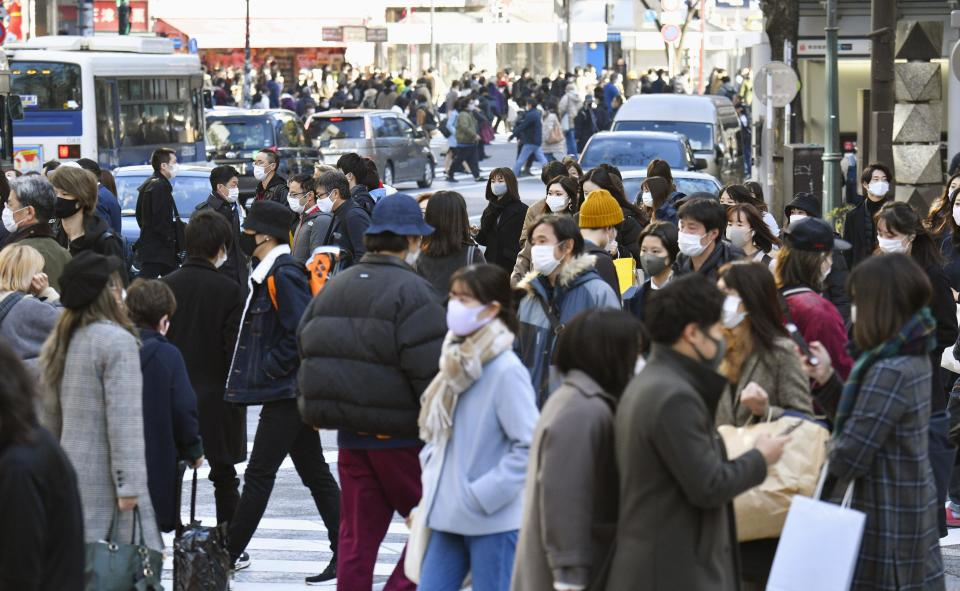 People wearing face masks to help curb the spread of the coronavirus cross a street in Shibuya district in Tokyo Monday, Dec. 28, 2020. Japanese Prime Minister Yoshihide Suga says he plans to submit legislation that will make coronavirus measures legally binding for businesses, punish violators and include economic compensation as his government struggles to slow the ongoing upsurge. (Kyodo News via AP)