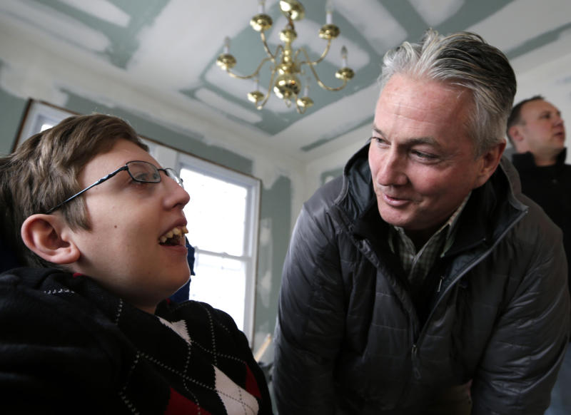 Connor Troy, 12, who suffers from a life-threatening neuromuscular disease, meets with Donald Denihan, at the Troy family home in Long Beach, N.Y., Wednesday, Dec. 12, 2012. Denihan is paying for repairs to the family's home while the family stays in another home in nearby Point Lookout, N.Y. He hopes they can move back in by Christmas. (AP Photo/Kathy Willens)