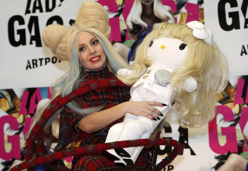 """Lady Gaga poses for photographers with a Hello Kitty doll during a press conference to promote her album """"ARTPOP"""" in Tokyo, Sunday, Dec. 1, 2013. The doll will be sold at an auction for donation to the northeastern Japanese regions hit by the 2011 earthquake and tsunami. (AP Photo/Shizuo Kambayashi)"""