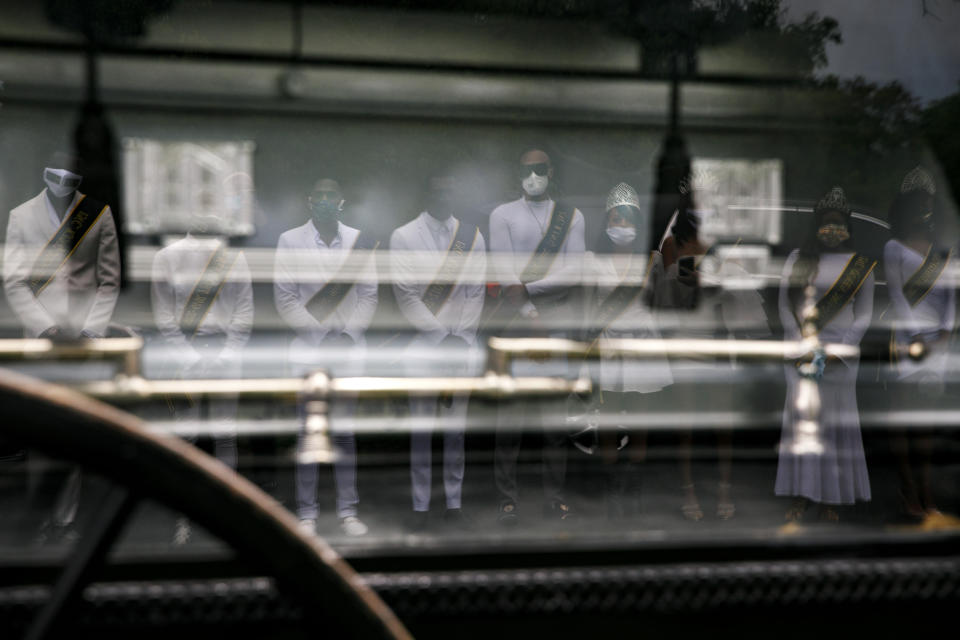 """Wearing sashes and tiaras, the Kings and Queens of Models Inc., are reflected in a horse drawn hearse from Compassion and Serenity Funeral Home as they pay their respects to Joanne Paylor, 62, of southwest Washington, during her funeral in Suitland-Silver Hill, Md., Sunday, May 3, 2020. Models Inc. is a community organization founded by Iran """"Bang"""" Paylor that was supported by his mother, Joanne Paylor. Despite not having died from coronavirus, almost every aspect of her funeral has been impacted by the pandemic. (AP Photo/Jacquelyn Martin)"""