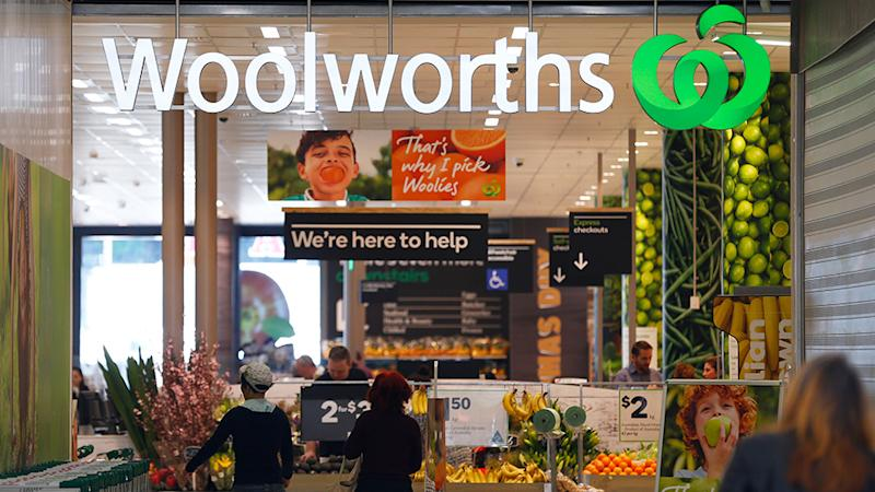 """Picture of a Woolworths, with a sign saying """"we're here to help"""". Woolworths utilises various forms of self-serve checkouts."""