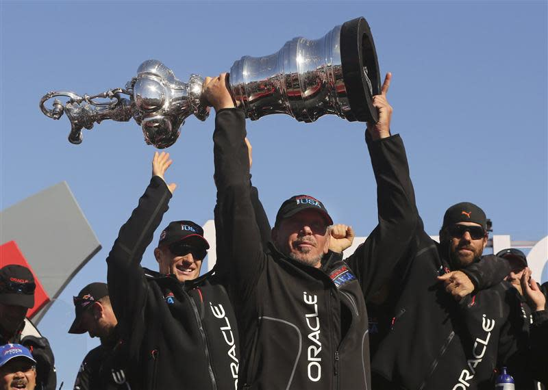 Oracle CEO Larry Ellison lifts the America's Cup with members of the Oracle Team USA after winning the overall title of the 34th America's Cup yacht sailing race over Emirates Team New Zealand in San Francisco