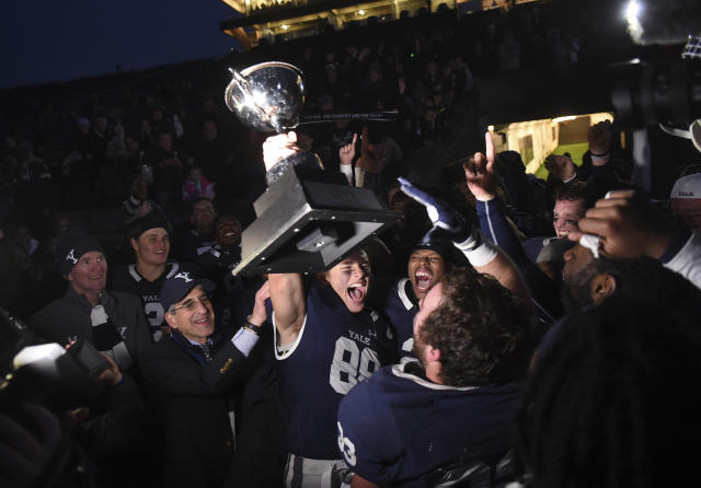 Yale's JP Shohfi, center, holds the Ivy League Championship trophy during a celebration with teammates after their 50-43 double overtime victory against Harvard in an NCAA college football game at the Yale Bowl, Saturday, Nov. 23, 2019, in New Haven, Conn. At left is Yale University president Peter Salovey. (Arnold Gold/New Haven Register via AP)