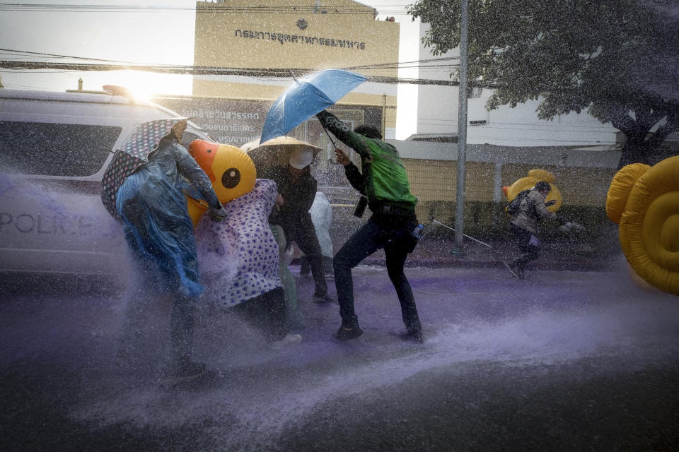 Pro-democracy protesters take cover with inflatable ducks and umbrellas as police fire water cannons during an anti-government rally near the Parliament in Bangkok, Tuesday, Nov. 17, 2020. Thailand's political battleground shifted to the country's Parliament Tuesday, where lawmakers are considering proposals to amend the country's constitution, one of the core demands of the student-led pro-democracy movement. (AP Photo/Wason Wanichakorn)