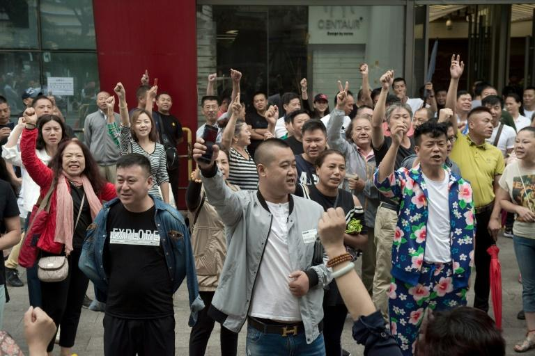 """The crowd gathered outside the entrance of the Beijing Zoo wholesale market in the west of the city, punching their fists in the air and shouting, """"Return our money!"""""""