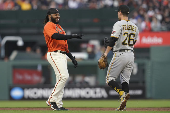 San Francisco Giants' Johnny Cueto, left, gets his helmet from Pittsburgh Pirates second baseman Adam Frazier (26) after stealing second base during the third inning of a baseball game in San Francisco, Friday, July 23, 2021. (AP Photo/Jeff Chiu)