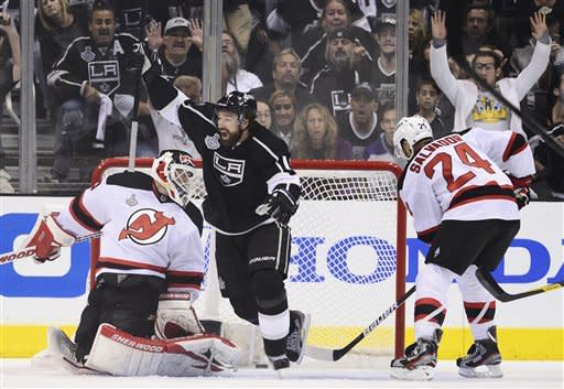 Los Angeles Kings right wing Justin Williams (14) reacts after Dustin Brown's first goal against New Jersey Devils goalie Martin Brodeur (30) as New Jersey Devils defenseman Bryce Salvador (24) looks on in the first period during Game 6 of the NHL hockey Stanley Cup finals,Monday, June 11, 2012, in Los Angeles. (AP Photo/Mark J. Terrill)