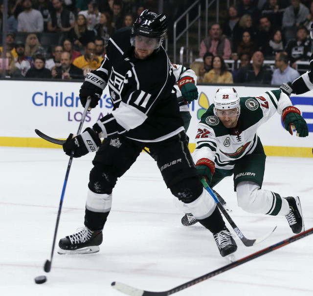 Los Angeles Kings center Anze Kopitar (11), of Slovenia, clears the puck under pressure from Minnesota Wild right wing Nino Niederreiter (22), of Switzerland, during the first period of an NHL hockey game in Los Angeles, Thursday, Nov. 8, 2018. (AP Photo/Alex Gallardo)