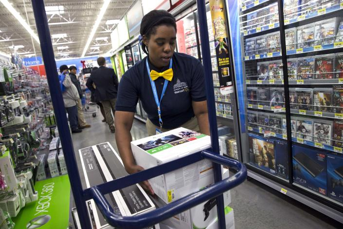 In this Wednesday, Dec. 4, 2013, photo, Tracey Anderson, 26, re-stocks X-Box sets on opening day of a new Wal-Mart on Georgia Avenue Northwest in Washington. Wal-Mart said Friday, Jan. 31, 2014, that its fiscal fourth-quarter and full-year adjusted earnings from continuing operations may come in at or slightly below the low end of its prior forecasts. (AP Photo/Jacquelyn Martin)