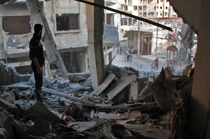 A Syrian man stands at a destroyed flat at the site of government air strikes which killed at least four civilians, including a child on November 2, 2017 in Douma, in the rebel-held Eastern Ghouta region outside Damascus
