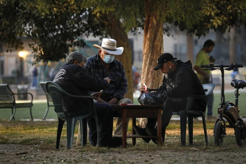 """Los Angeles, California-Nov. 19, 2020-California will impose """"limited"""" curfew due to COVID-19 surge. People gather outside, some playing cards, at MacArthur Park on Nov. 19, 2020 at 5:00pm. (Carolyn Cole / Los Angeles Times)"""