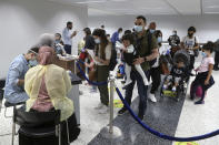 Passengers wait in line to fill a document to undergo a PCR test at the Rafik Hariri International Airport in Beirut, Lebanon, Wednesday, July 1, 2020. Beirut's airport is partially reopening after a three-month shutdown and Lebanon's cash-strapped government is hoping that thousands of Lebanese expatriates will return for the summer, injecting dollars into the country's sinking economy. (AP Photo/Bilal Hussein)Hussein)