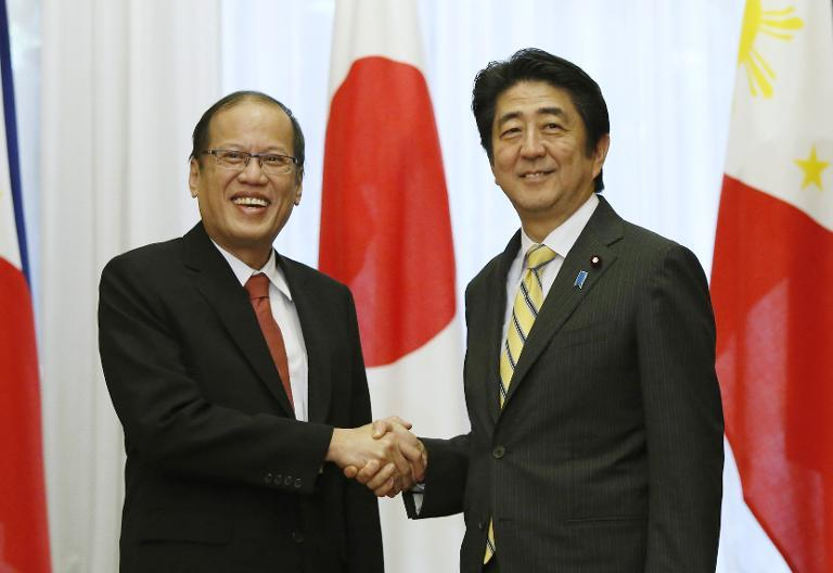 Philippines' President Benigno Aquino (L) is greeted by Japan's Prime Minister Shinzo Abe at the start of their meeting in Tokyo, on June 24, 2014