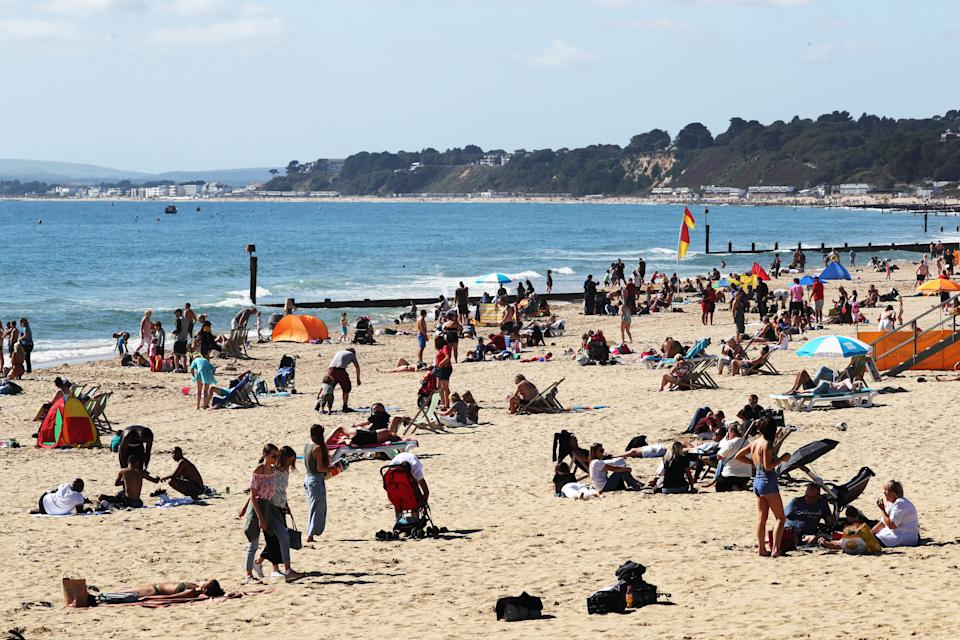 Visitors at Bournemouth beach have taken to the sand to make the most of the hot weekend weather across the UK. (Photo by Jonathan Brady/PA Images via Getty Images)