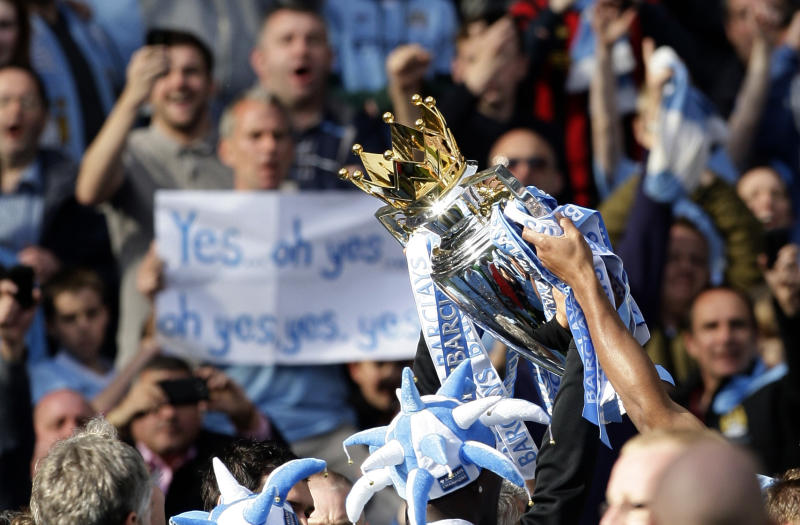 Manchester City players parade the English Premier League trophy after their 3-2 win over Queens Park Rangers at The Etihad Stadium, Manchester, England, Sunday May 13, 2012. In winning the game Manchester City won the English Premier League for the first time in 44 years. (AP Photo/Jon Super)