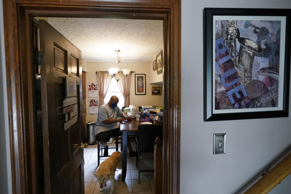 Larry Brown sits at the kitchen table at his parents house, Thursday, Aug. 27, 2020, in Indianapolis. Recovering from COVID-19, Brown still has to stretch his hands and legs, which stiffen up frequently. (AP Photo/Darron Cummings)