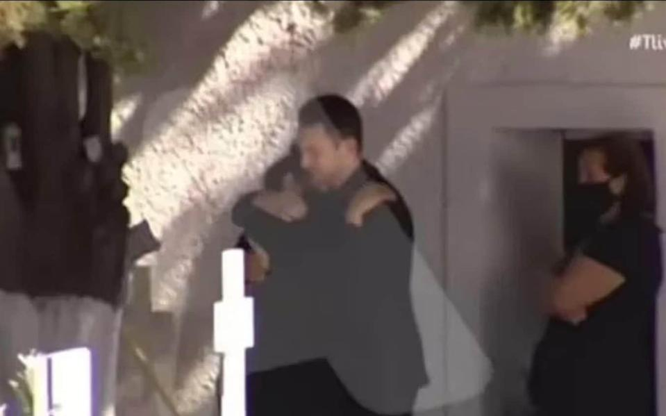 Babis Anagnostopoulos hugs his grieving mother-in-law at his wife's memorial service, just hours before he admitting to her murder