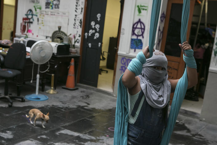 A 10-year-old victim of sexual abuse, who keeps her face covered to hide her identity, poses for a photo while playing with aerial fabric inside the Mexican Human Rights Commission (CNDH) headquarters where she has been living with her mother, also a victim of sexual abuse when she was a child, after women's rights activists occupied the building and turned it into a refuge almost three months prior in Mexico City, Tuesday, Nov. 17, 2020. The girl's mother Erika Martinez said she filed a complaint three years ago with the Prosecutor for Sexual Crimes after her daughter was abused at age 7 by her brother-in-law, but that the man remains free. (AP Photo/Ginnette Riquelme)