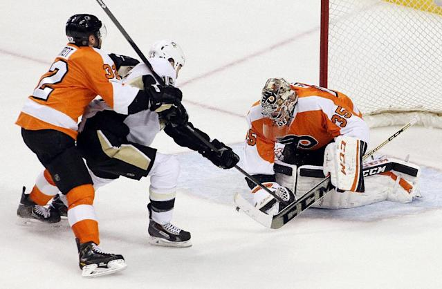 Philadelphia Flyers goalie Steve Mason covers up the puck as Pittsburgh Penguins' Tanner Glass, center, tries to poke it free as Mark Streit follows him during the third period of an NHL hockey game, Saturday, March 15, 2014, in Philadelphia. The Flyers won 4-0. (AP Photo/Tom Mihalek)