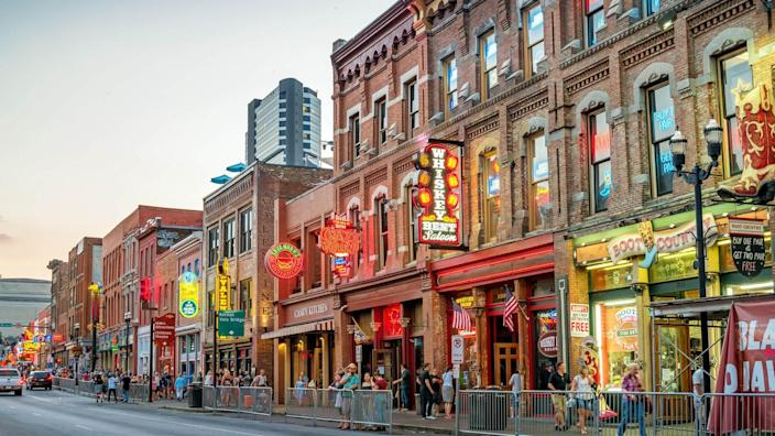 People enjoy a pleasant evening in the Broadway pub district, downtown Nashville, Tennessee, USA at twilight.