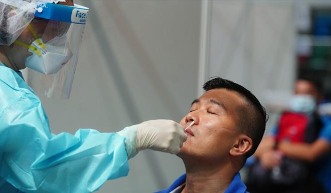 A resident undergoes testing at the Queen Elizabeth Stadium in Wan Chai. Photo: Sam Tsang
