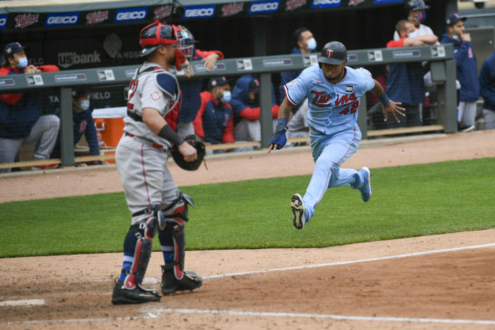 Minnesota Twins' Jorge Polanco, right, races home to scores the winning run on a single by Max Kepler as Boston Red Sox catcher Christian Vazquez waits for the throw in the ninth inning of a baseball game, Thursday, April 15, 2021, in Minneapolis. The Twins won 4-3. (AP Photo/Craig Lassig)