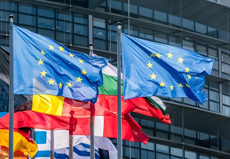European flags flying in front of a building.