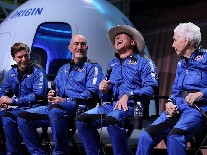 Blue Origin's New Shepard crew is seen in blue flight outfits sitting in front of the shuttle's capsule.ª