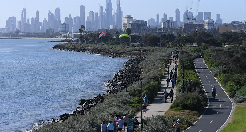People are seen walking near the water with Melbourne's CBD in the background. Source: AAP