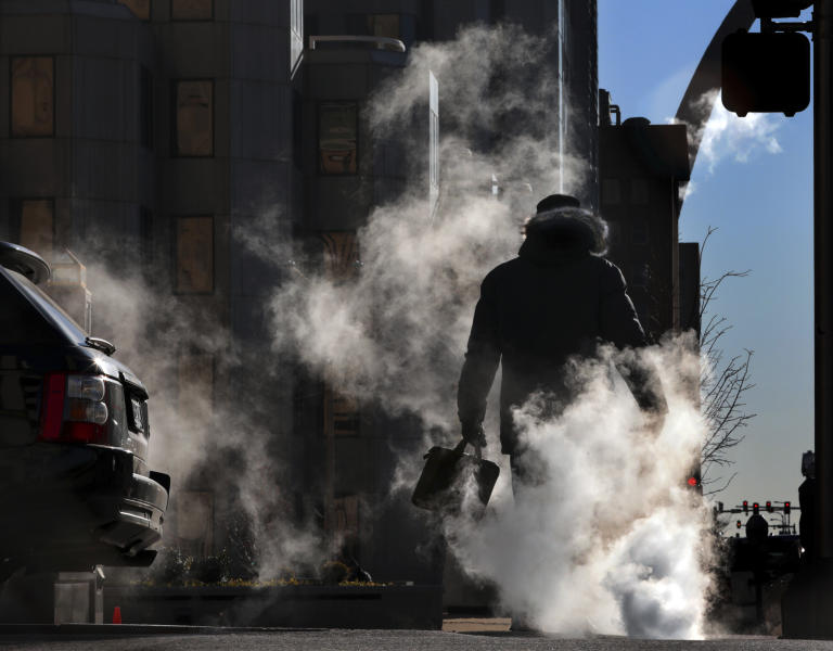A worker makes his way through a steam cloud rising from underground utilities as morning temperatures hovered in the single digits, Friday, Feb. 14, 2020, in downtown St. Louis, Mo. (Robert Cohen/St. Louis Post-Dispatch via AP)