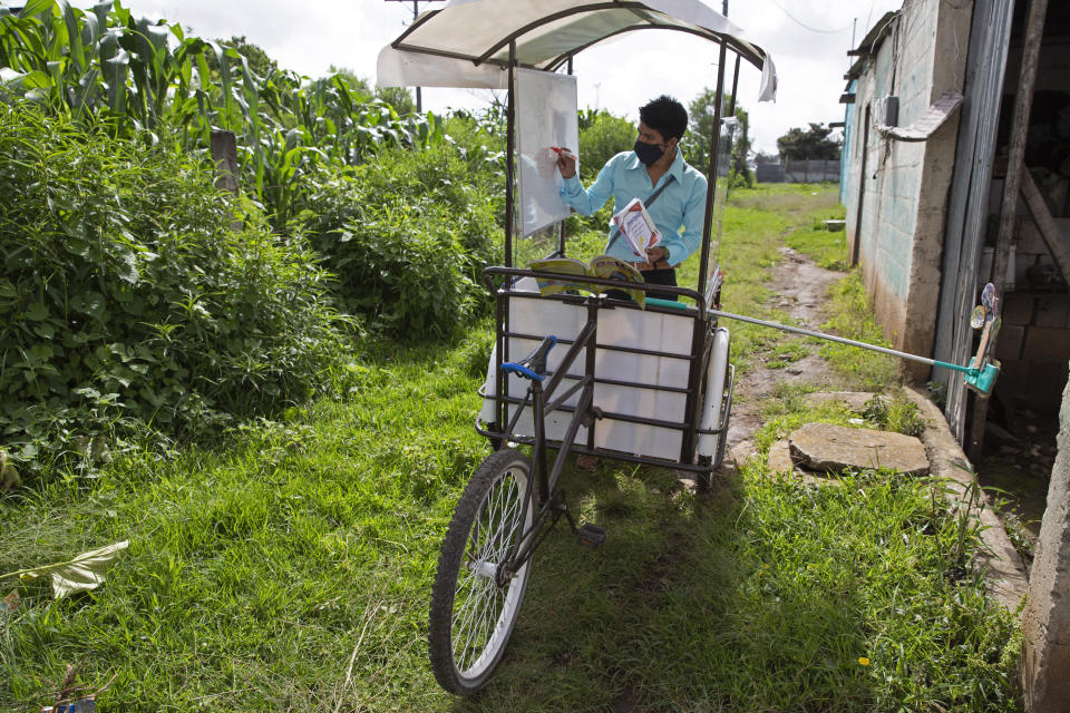 Teacher Gerardo Ixcoy conducts a math class from a secondhand, adult tricycle that he converted into a mobile classroom, in Santa Cruz del Quiche, Guatemala, Wednesday, July 15, 2020, amid the new coronavirus pandemic. The 27-year-old teacher deploys a sponge mop to serve as a safe distance reminder between him and his students. (AP Photo/Moises Castillo)