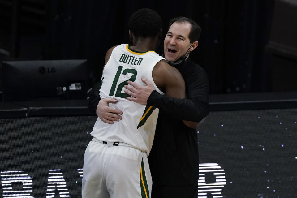 Baylor guard Jared Butler (12) gets a hug from head coach Scott Drew during the second half of a men's Final Four NCAA college basketball tournament semifinal game against Houston, Saturday, April 3, 2021, at Lucas Oil Stadium in Indianapolis. (AP Photo/Michael Conroy)