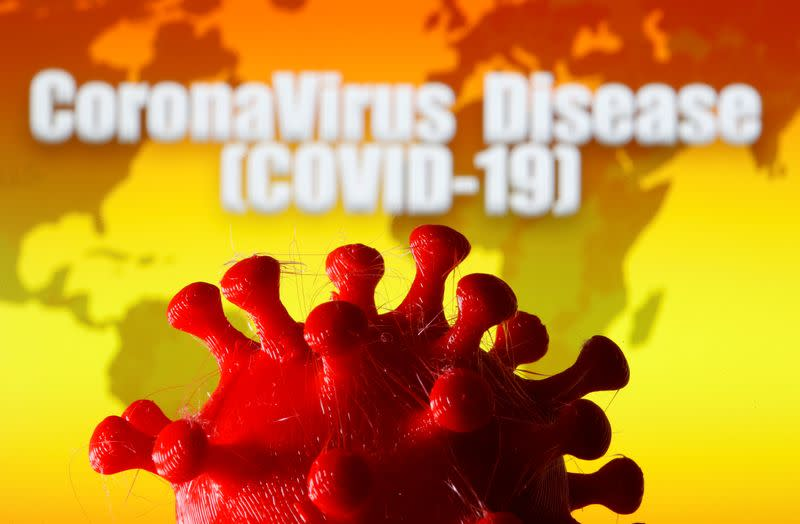 """A 3D-printed coronavirus model is seen in front of a world map and the words """"CoronaVirus Disease (Covid-19)"""" on display in this illustration"""