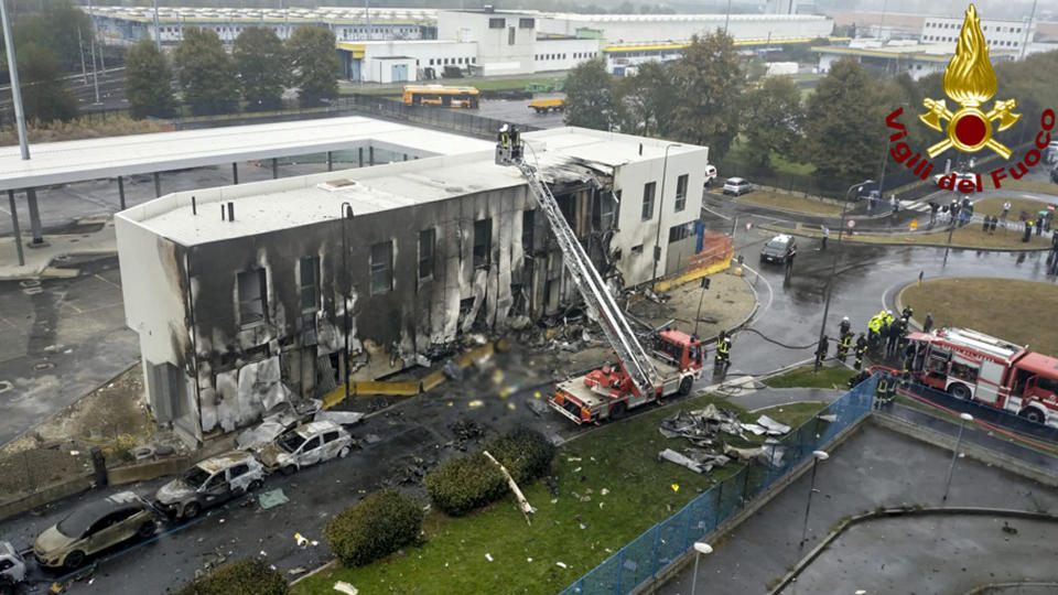 Firefighters work on the site of a plane crash, in San Donato Milanese suburb of Milan, Italy, Sunday, Oct. 3, 2021. A small private plane has crashed into a vacant office building in a Milan suburb. Italian news reports said all eight persons aboard were killed. Firefighters tweeted that no one other than those aboard were involved in the crash Sunday afternoon near a subway station in San Donato Milanese. (Vigili del Fuoco via AP)