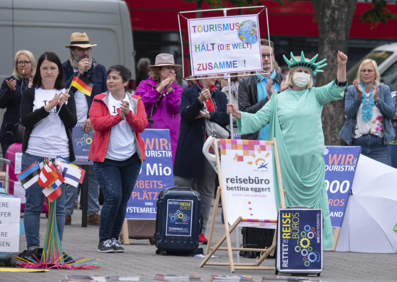 A woman dressed as New York's Statue of Liberty attends a demonstration of the tourism business at the cathedral square in Erfurt, Germany, Wednesday, May 20, 2020. Representatives of coach companies, travel agencies and tour operators protest to draw attention to the difficult situation caused by the ban on employment since the new coronavirus outbreak. Slogen on her protest poster reads: 'Tourism keeps the world together'. (AP Photo/Jens Meyer)