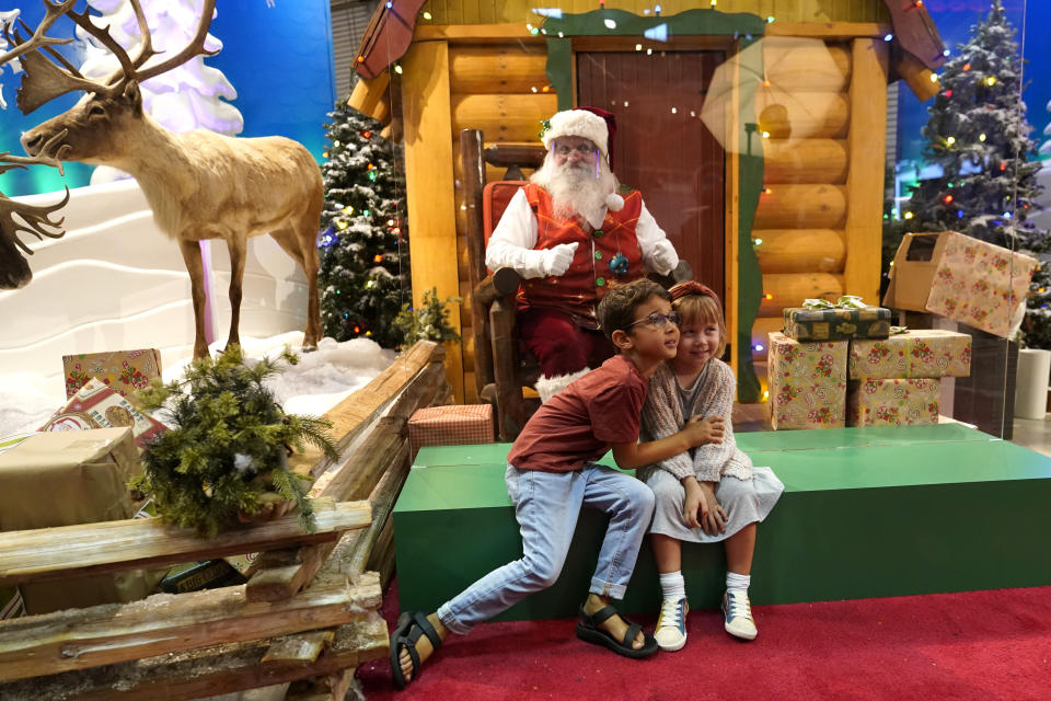 Theo and Sophy Morris, visiting from Hawaii with their family, pose for a photograph with Santa Claus, who is sitting behind a transparent barrier, at Bass Pro Shops in Miami on Nov. 20, 2020. In this socially distant holiday season, Santa Claus is still coming to towns (and shopping malls) across America but with a few 2020 rules in effect. (AP Photo/Lynne Sladky)
