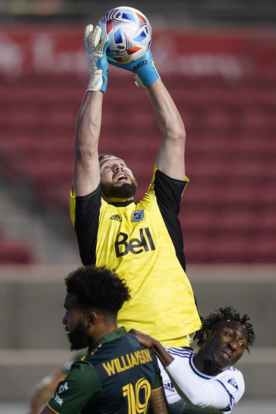 Vancouver Whitecaps goalkeeper Maxime Crepeau, rear, makes a save as teammate Janio Bikel, right, defends against Portland Timbers forward Eryk Williamson (19) in the first half during an MLS soccer game Sunday, April 18, 2021, in Sandy, Utah. (AP Photo/Rick Bowmer)