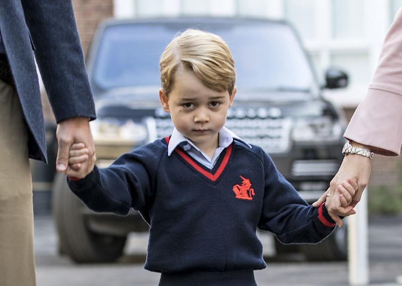 Prince George holding hands with his family.