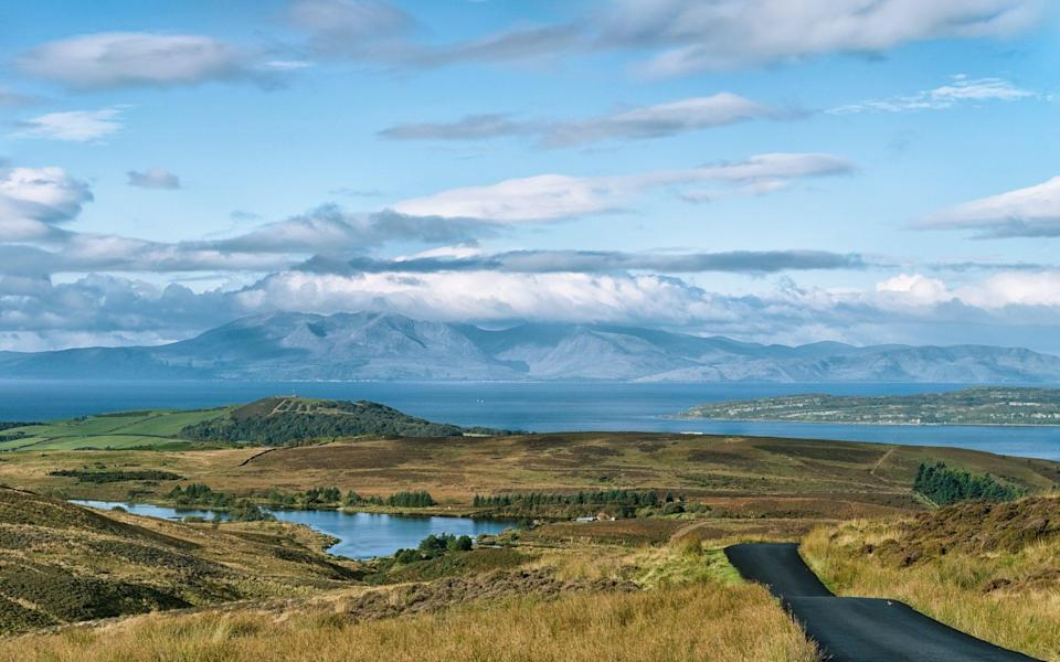 Hills, touched by clouds in distance, with water and rolling green in front of it - jimmcdowall/iStockphoto