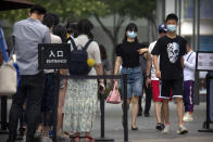 People wearing face masks to protect against the new coronavirus walk past a line of people waiting to show the results of a smartphone health check app before they can enter an outdoor shopping mall in Beijing, Saturday, July 4, 2020. China reported a single new case of coronavirus in Beijing on Saturday, plus a few more cases elsewhere believed to have come from abroad. (AP Photo/Mark Schiefelbein)