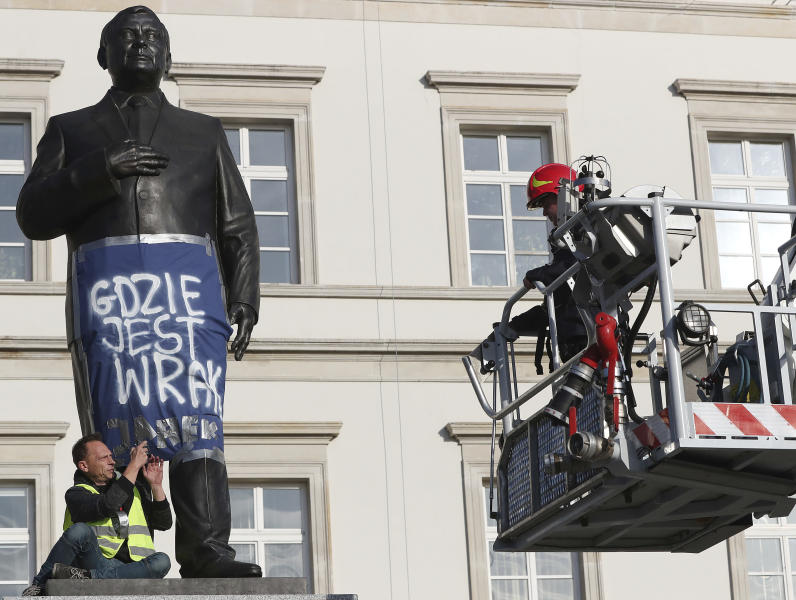 A man sits on a monument to Poland's late president Lech Kaczynski in downtown Warsaw, Poland, Friday, Oct. 11, 2019. He wrapped it in a banner reading 'Where is the Wreckage?' of the plane that crashed in 2010 in Russia, killing the president. Just two days ahead of parliamentary elections, this is criticism of the ruling Law and Justice party, led by the late president's twin Jaroslaw Kaczynski, which has vowed to bring the wreckage back from Russia, where it remains. (AP Photo/Czarek Sokolowski)