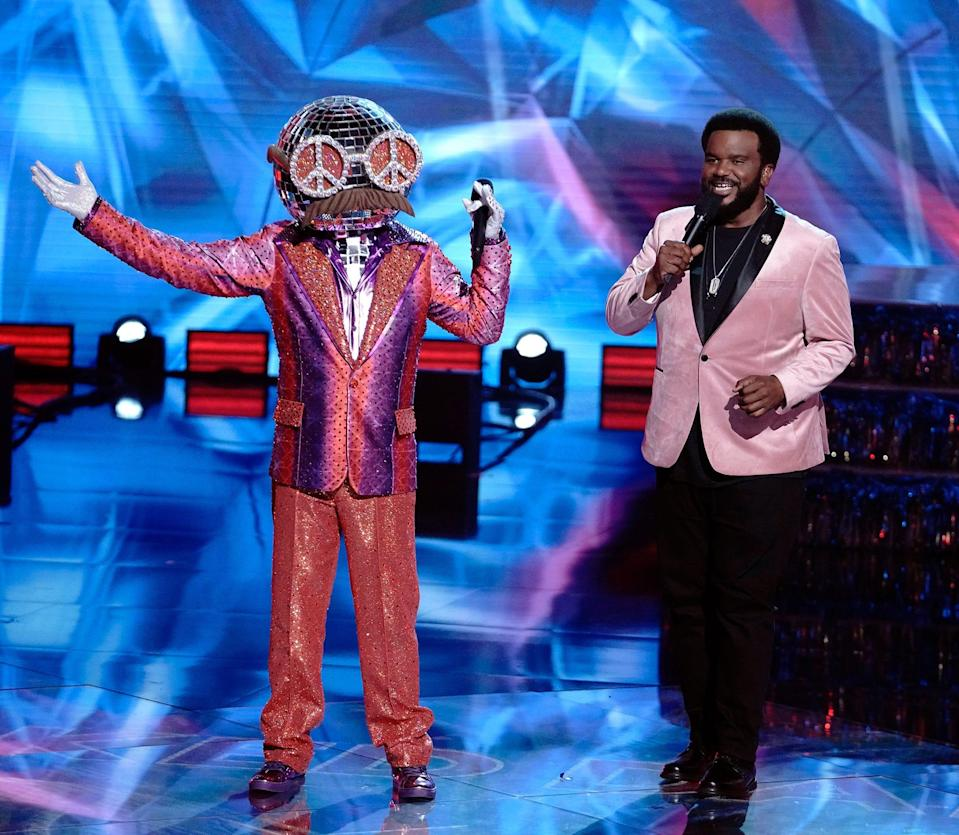 """Disco Ball, left, and host Craig Robinson appear during an episode of Fox's """"The Masked Dancer."""""""