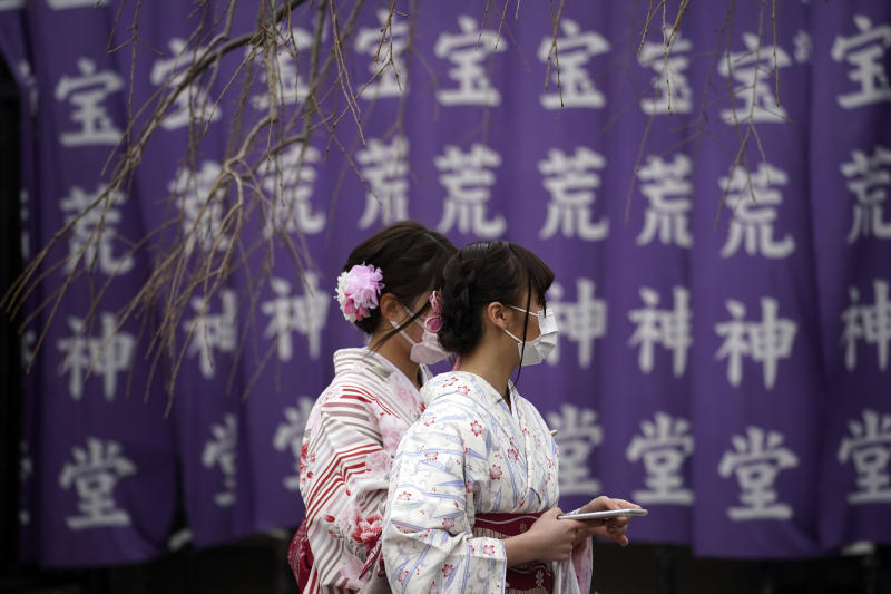 Visitors wear protective masks Wednesday, Feb. 26, 2020, in Tokyo. At a government task force meeting Wednesday on the virus outbreak, Japan's Prime Minister Abe said he was asking organizers to cancel or postpone major sports or cultural events over the next two weeks. (AP Photo/Eugene Hoshiko)
