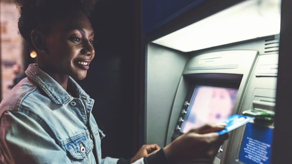 Cheerful African-American woman using her bank card at the ATM in the evening.