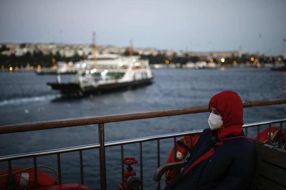 FILE - In this Wednesday, Oct. 21, 2020, file photo, a woman, wearing a protective mask to help prevent the spread of the coronavirus, takes a boat trip over the Bosphorus Strait separating the Asian and the European sides of Istanbul. When Turkey changed the way it reports daily COVID-19 infections, it confirmed what medical groups and opposition parties have long suspected — that the country is faced with an alarming surge of cases that is fast exhausting the Turkish health system. The official daily COVID-19 deaths have also steadily risen to record numbers in a reversal of fortune for the country that had been praised for managing to keep fatalities low. With the new data, the country jumped from being one of the least-affected countries in Europe to one of the worst-hit. (AP Photo/Emrah Gurel, File)